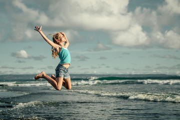 teen girl  jumping on the beach at blue sea shore in summer vaca