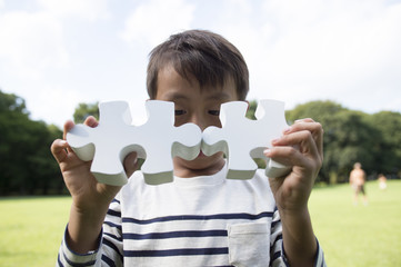 Boy with two pieces of the puzzle