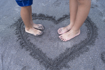 Boys and girls to write a heart on the beach