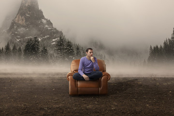 Crisis. Man in armchair in a foggy field with mountains behind