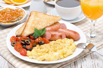 scramble eggs with tomatoes, sausage and toast on a plate