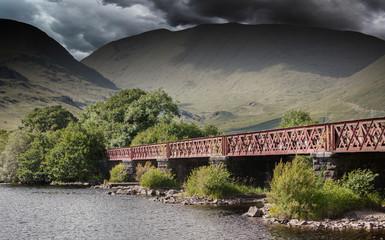 Structure of metal railway bridge, stormy clouds