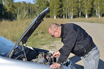 Мужчина ремонтирует автомобиль.