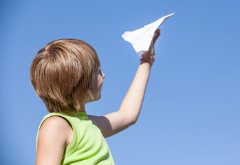 young boy with paper plane against blue sky