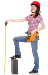 Smiling woman in helmet with tape measure and tools