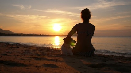 Silhouette of a Young Woman with Dog at Sunrise. Slow Motion.