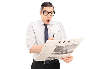 Shocked man reading the news through a magnifier