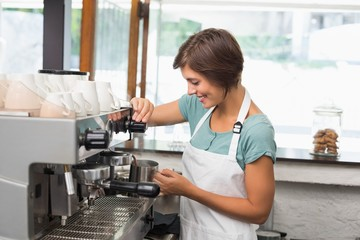 Pretty barista steaming jug of milk at coffee machine