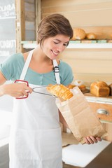 Pretty waitress putting croissant in paper bag