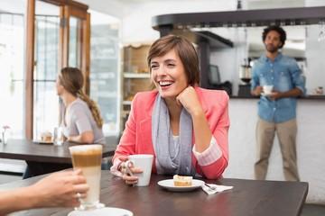Pretty brunette enjoying her latte with a friend