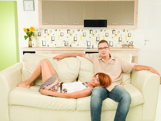 happy couple relaxing on sofa