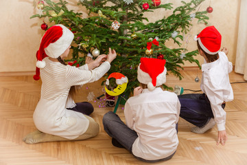 boys and girl decorate christmas tree