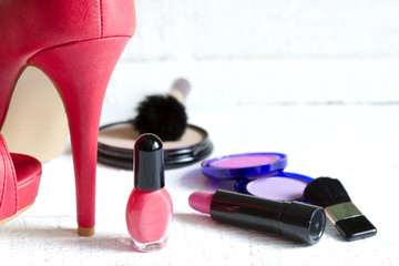High red heels and set of cosmetics abstract on white planks