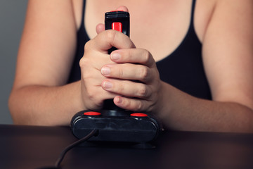 Young woman plays video game with a retro joystick