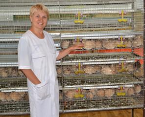 The joyful female farmer shows on a cage with quails
