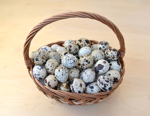 Quail eggs in a wattled basket on a light background, the top vi