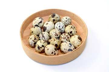 Quail eggs in a birch bark bast basket on a white background