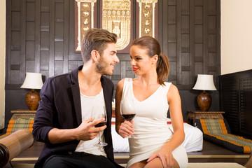 Verliebtes Paar beim Weintrinken im asiatischen Hotelzimmer