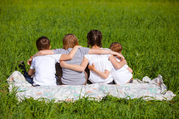 Back view of cute kids seated on green grass and relaxing