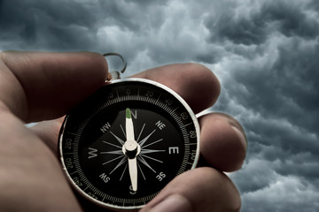 Hand holding black compass