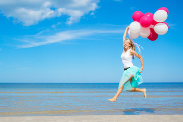 Happy woman holding balloons and jumping in the air