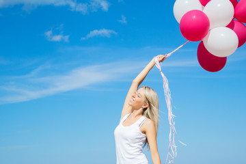 Happy young woman holding balloons in clear blue sky