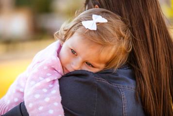 Girl child on a shoulder at mother