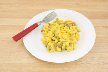 Mac and cheese meal on paper plate with fork