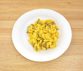 Macaroni and cheese with meat on a paper plate
