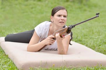 jeune fille avec air carabine contre champ
