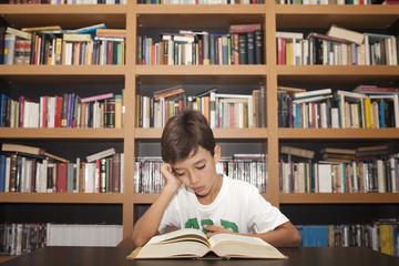 Niño leyendo libro junto a librería