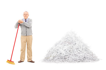 Senior standing by a pile of shredded paper