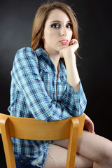 Teenager sitzt nachdenklich auf Stuhl