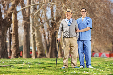 Senior man and a male nurse posing in park