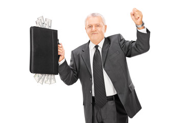 Mature businessman holding briefcase full of cash
