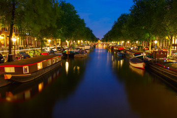 Night city view of Amsterdam canal with Houseboat