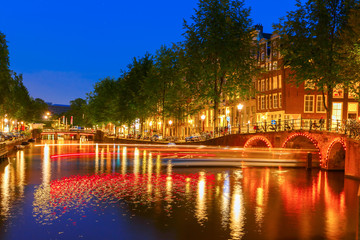 Night city view of Amsterdam canal and luminous track from the b