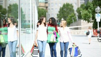 three young multi-ethnic women shopping in town slow motion.