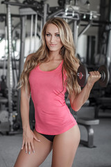Woman holding dumbbell in gym