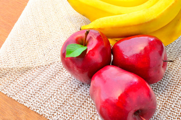 group of red apples and bunch of banana