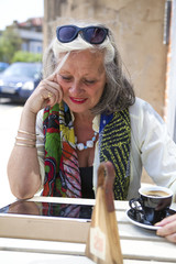 Mature woman unsing mobile device in cafe
