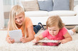 Kids Using Tablet Lying On Carpet