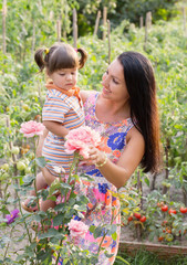 happy women and little child with roses outdoor