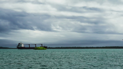 Ferry Passes by the Cargo Ship, cloudy weather