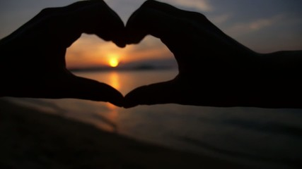Sunset Heart from Hands of Love Couple on Beach. Slow Motion.
