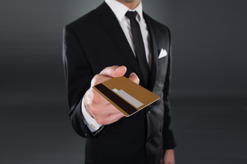 Midsection Of Businessman Giving Credit Card
