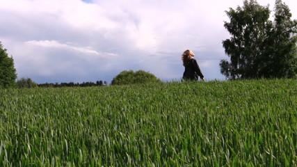 woman with dark jacket go through wide crop field in summer