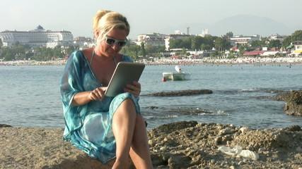 Woman using digital tablet on the beach
