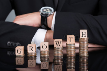 Businessman With Growth Blocks On Stacked Coins