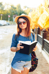 Beautiful girl tourist stands on the street with a notebook